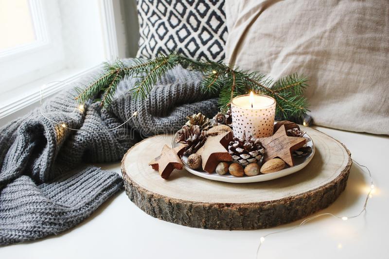 Winter festive still life scene. Burning candle decorated by wooden stars, hazelnuts and pine cones standing near window. On wooden cut board. Glittering royalty free stock photo