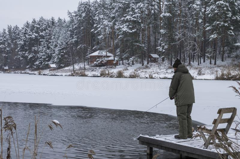 Winter fishing concept. Fisherman in action at the lake in forest. Winter fishing. Fisherman in action at the lake in forest royalty free stock photo