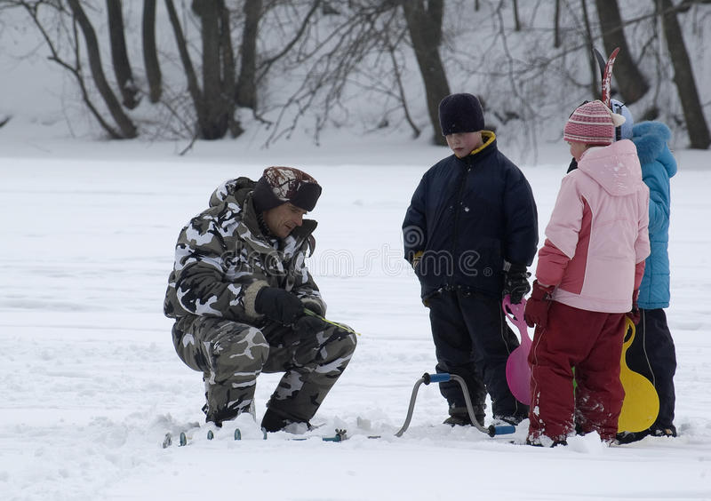 Winter fishing. Old Fisherman and young spectators stock image