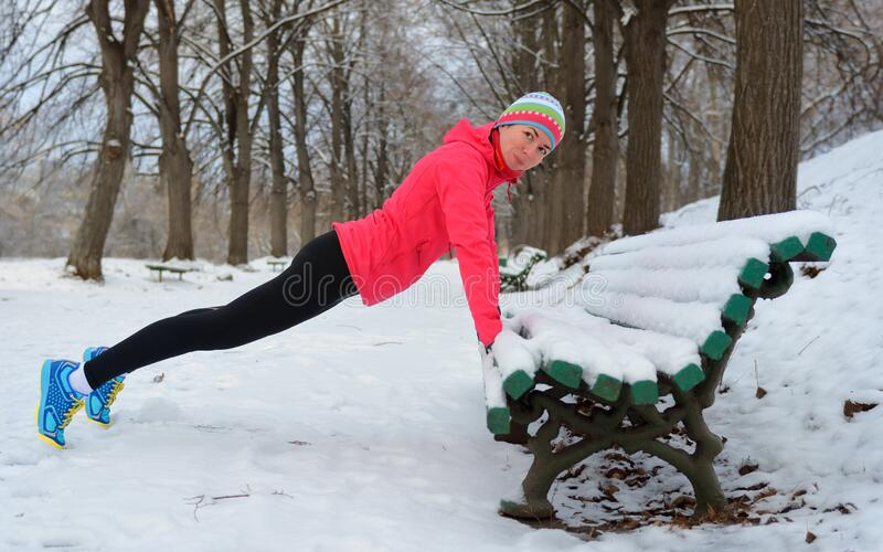Winter fitness and running in park: happy woman runner warming up and exercising before jogging in snow stock photo