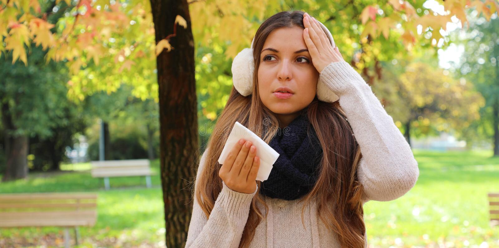 Winter flu banner view. Young woman suffering flu headache cold fever migraine holding tissue outdoors stock photos