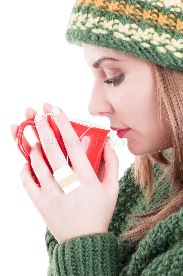 Winter flu or cold concept on white advertising area background. Young woman drinking hot tea and wearing warm clothes royalty free stock image