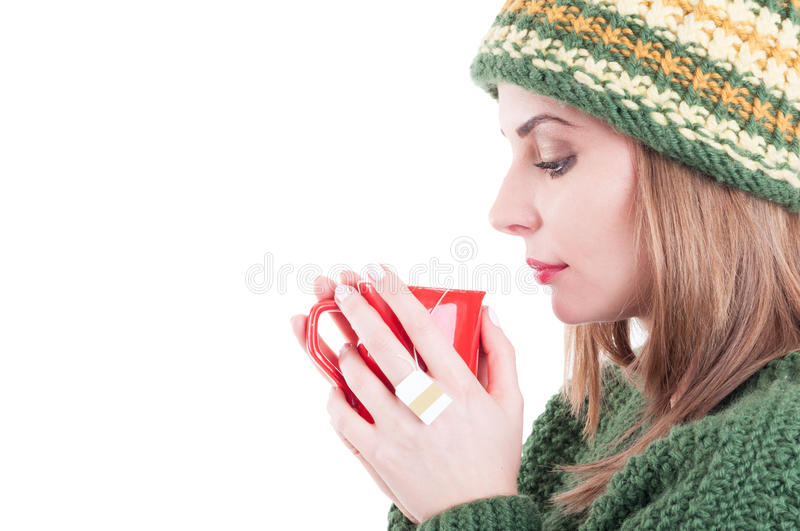 Winter flu or cold concept on white copy space background. Young woman drinking hot tea and wearing warm clothes stock images