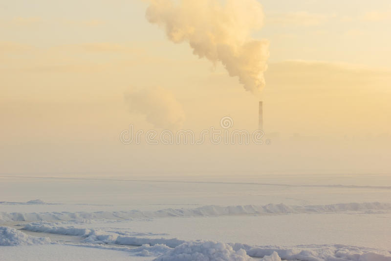 Winter fog over the frozen river and the factory pipe. A sudden fog on a cold day royalty free stock photography
