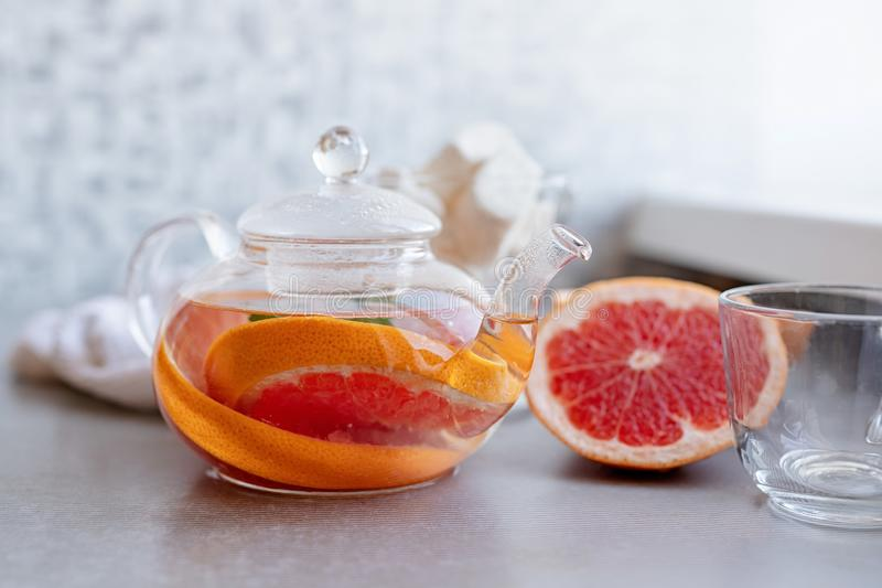 Hot grapefruit herbal tea with mint in a glass pot stock photography
