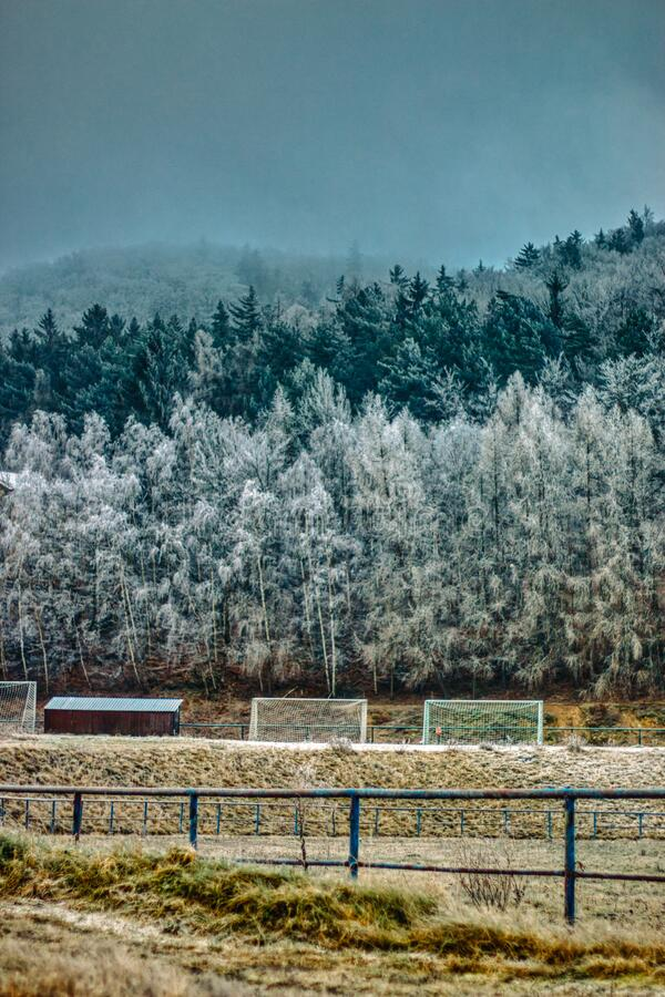 Winter football field with frosted mountains in background and goals. And frozen grass stock photo