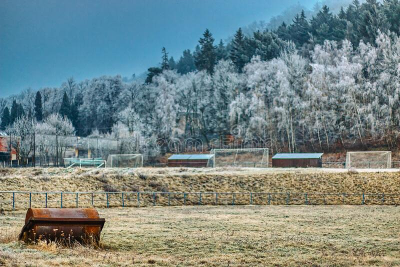 Winter football field with frosted mountains in background and goals. And frozen grass royalty free stock photo