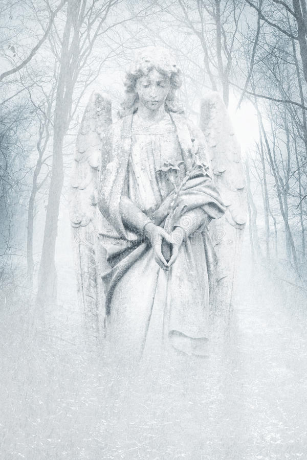 Winter Forest Angel. Angelic female figure materialising in an atmospheric misty winter forest rendered in cool blue tones stock image