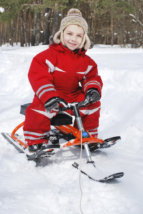 In winter, in the forest boy is sitting on a sled and smiling. stock photo