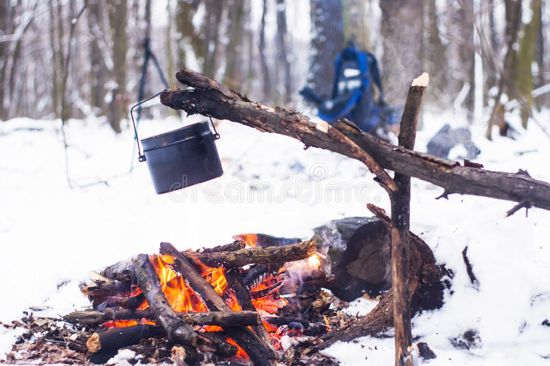 Winter forest, the tourist warm tea in a pot. Snow stock images