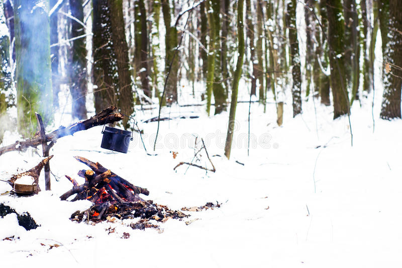 Winter forest, the tourist warm tea in a pot. Snow stock photos
