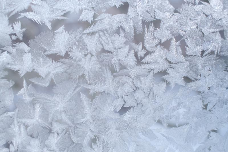 Winter frosty pattern on window pane with big fancy snowflakes. royalty free stock photos