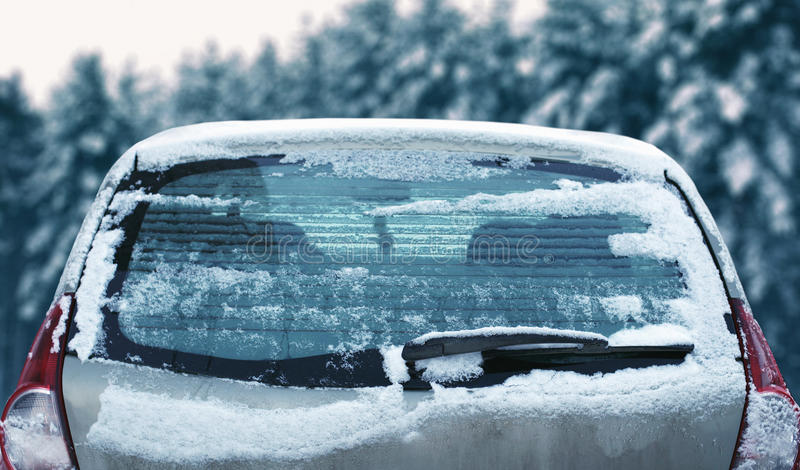 Winter frozen back car window, texture freezing ice glass with snow over snowy stock photos