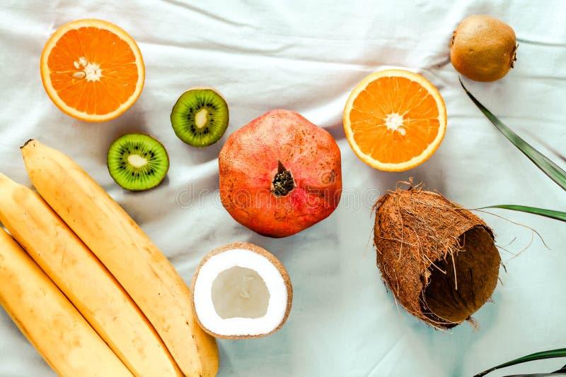 Winter fruits - pomegranates coconut kiwi, oranges. Top view. stock photography