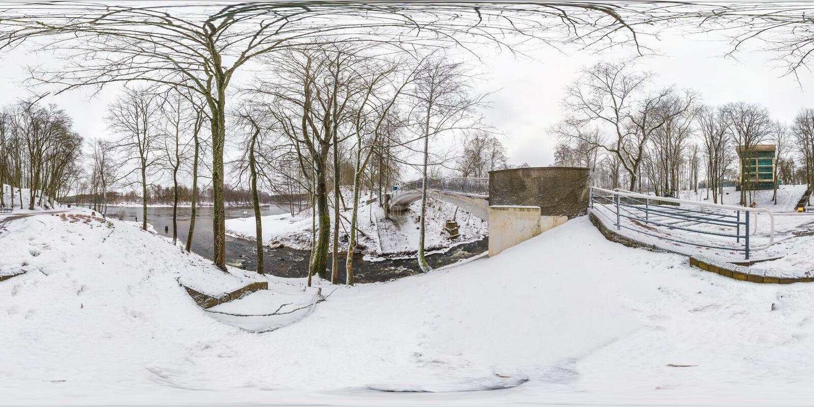 Winter full spherical seamless hdri panorama 360 degrees angle view in snowy park near the bridge of small river with gray pale royalty free stock photography