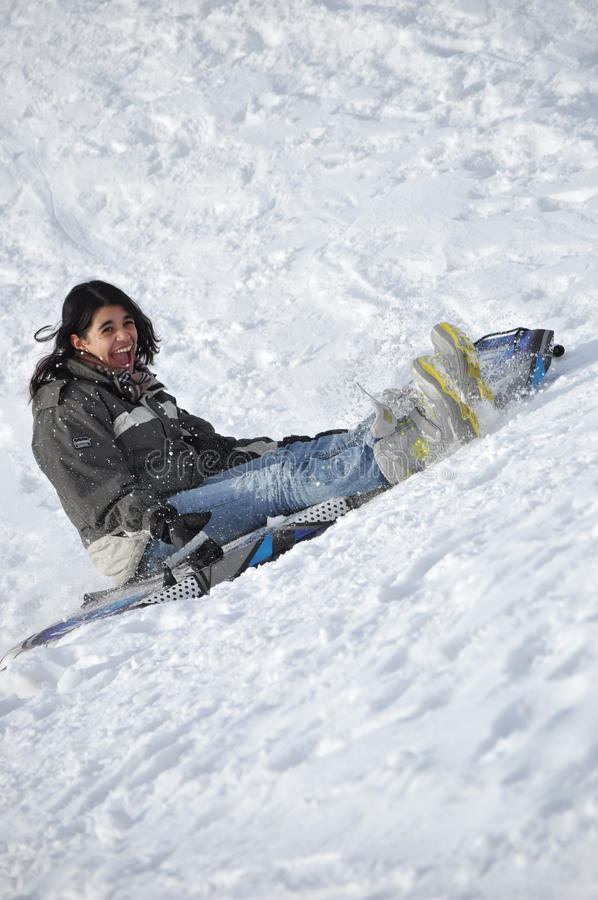 Latin Girl Sliding Down a Snowy Hill at a Great Sp stock photo
