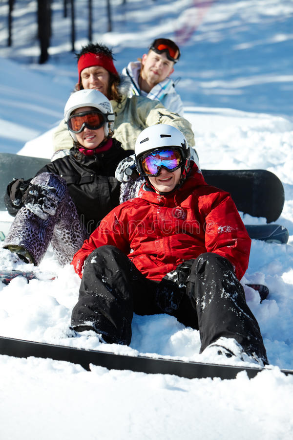 Winter fun. Portrait of happy friends snowboarding during winter vacations stock photo