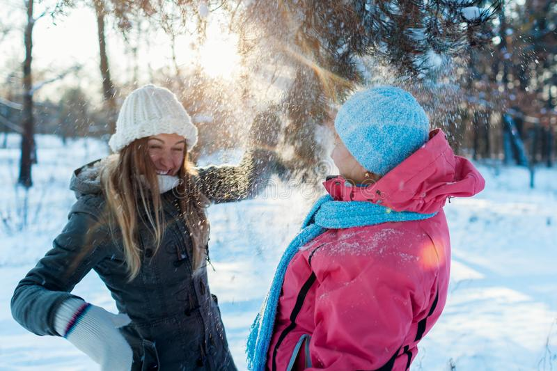 Winter fun activities. Mother and adult daughter shaking branches with snow outdoors. Family relaxing for holidays stock photography