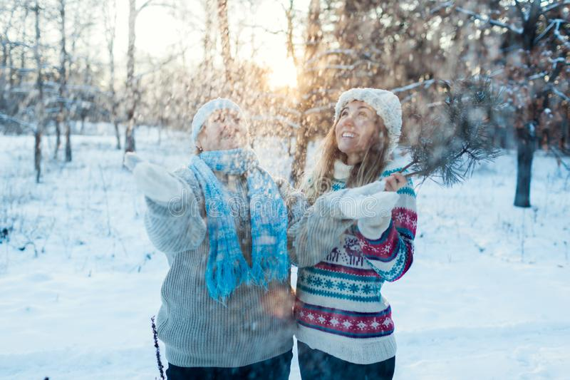 Winter fun activities. Mother and adult daughter throwing snow outdoors. Family relaxing in forest for holidays stock images