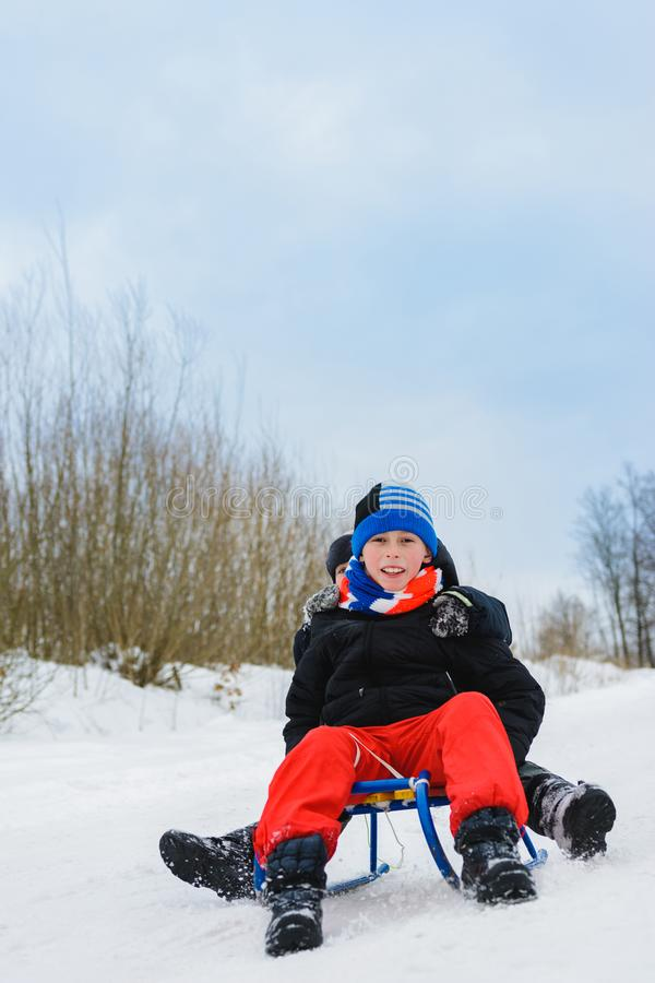 For winter fun entertainments two children ride on sleighs royalty free stock image