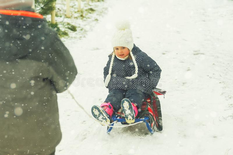 Family playing outdoors in the snow. Outdoor activities for family winter holidays. Winter fun in the fresh air . A little girl on a sled.Brother rubs sister royalty free stock images