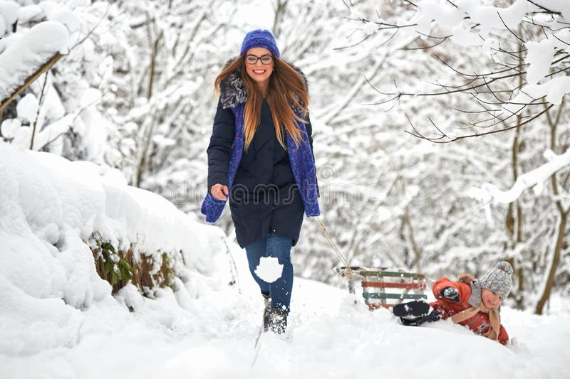 Winter fun. a girl and a boy are sledding. stock images