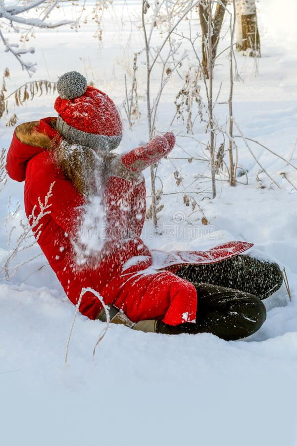 Winter fun. Girl in red sits on white snow and covers her face with her hands from the snow flying in her stock photos
