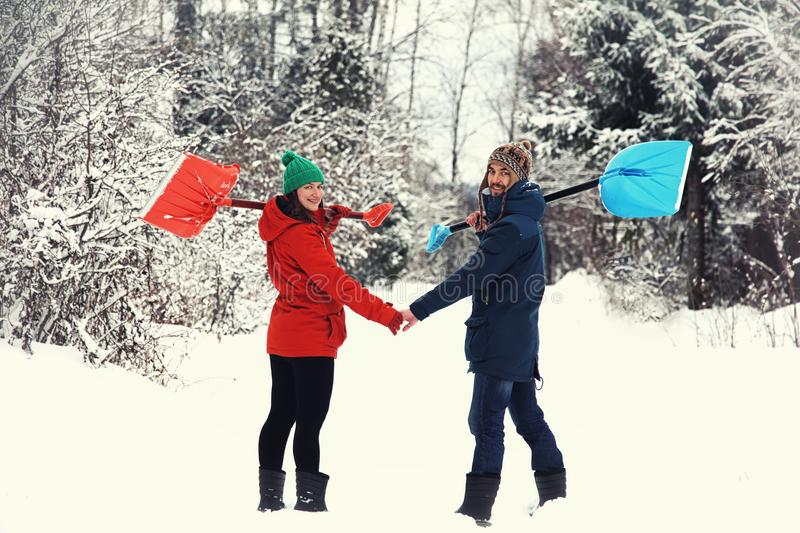 Winter fun: happy couple with snow shovels. Happy couple with snow shovels on rural road. Winter fun stock image