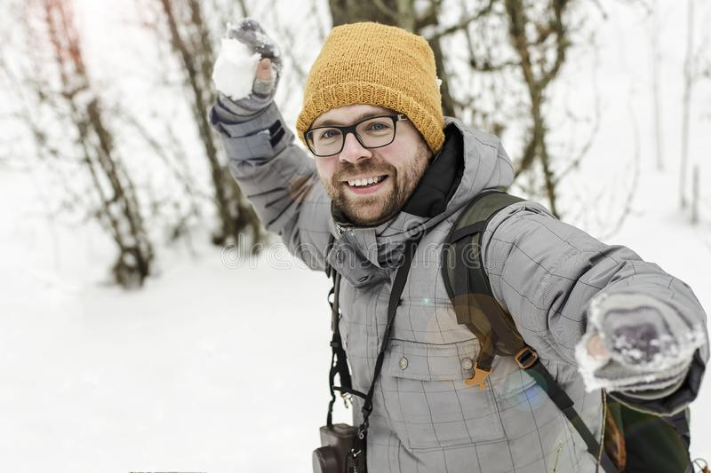 Winter fun. Joyful bearded man with a camera and a backpack is p royalty free stock photography