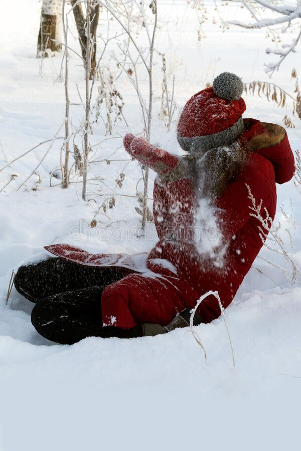 Winter fun. Young woman in red sits on white snow and covers her face with her hands from the snow flying in her stock photo