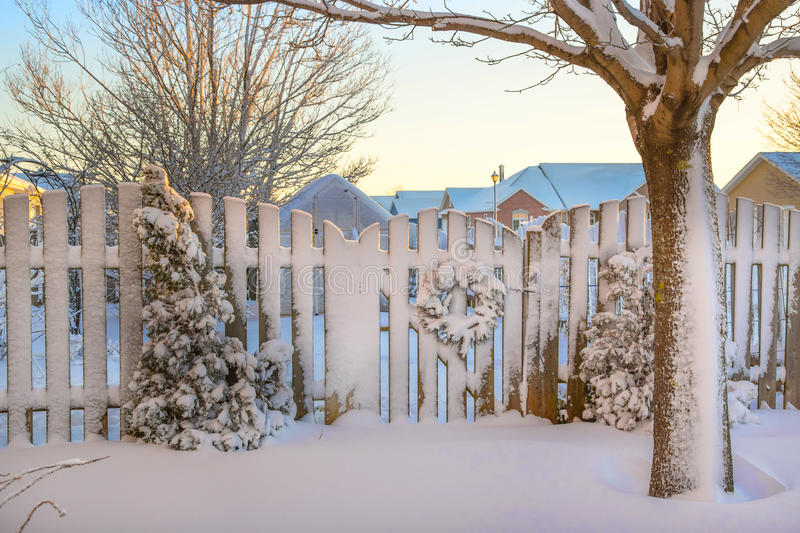 Winter Garden Gate. A garden gate decorated with a Christmas wreath all covered in snow royalty free stock photo