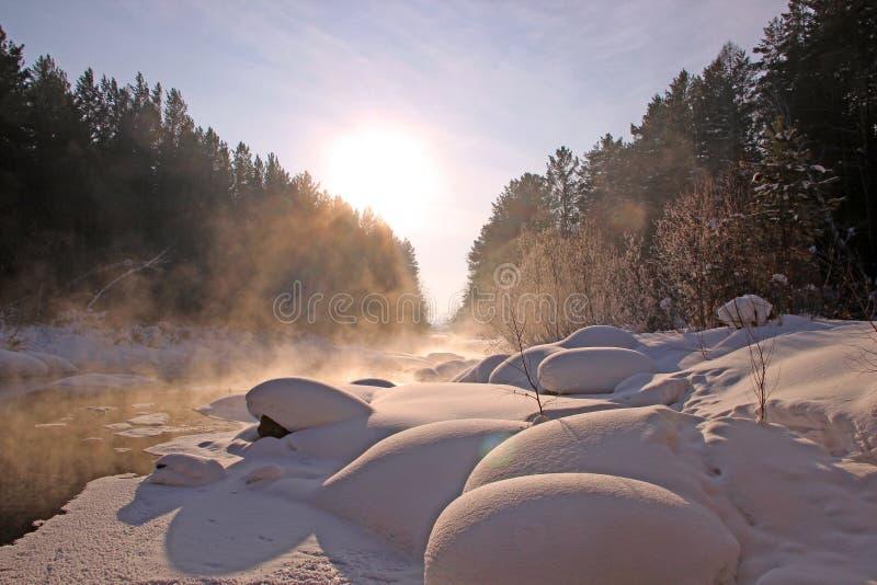 Winter gefrorener Fluss verengt zum Horizont und Nebel steigt vom Wasser stockbild