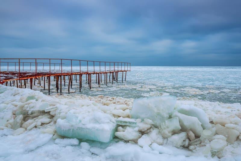 Winter gefrorenes Seeufer und der alte Pier stockfotografie