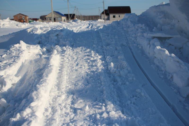 Winter geklärte Straßenreise unter den Schneewehen im Winter im sibirischen Dorf lizenzfreies stockbild