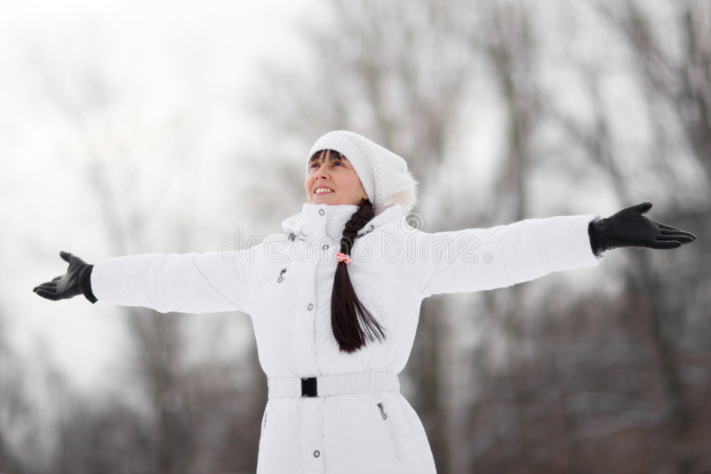 Winter girl. Winter portrait of a happy girl with arms spread - Shallow DOF royalty free stock photography