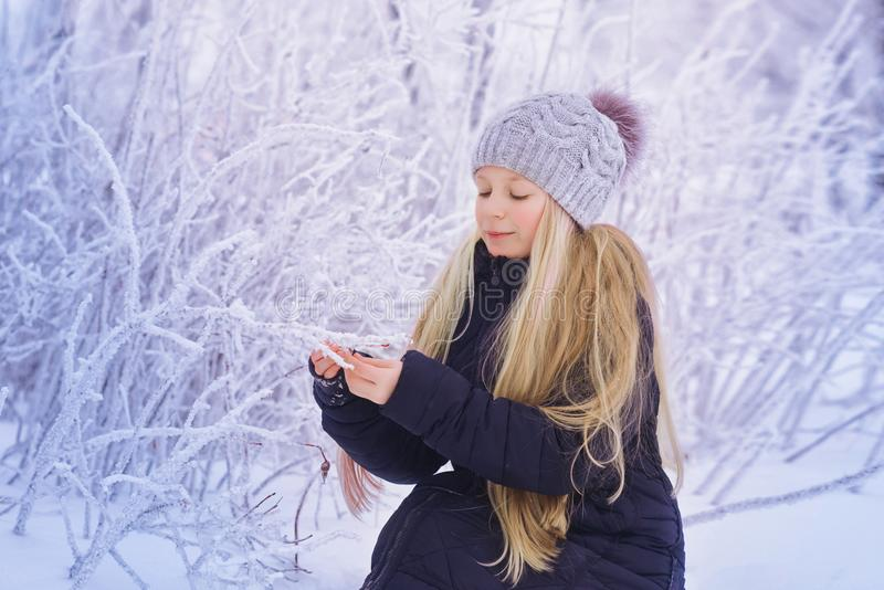 Winter girl blowing snow. Beauty Joyful Teenage Model Girl having fun in winter park. Beautiful girl laughing outdoors. Enjoying n stock photo