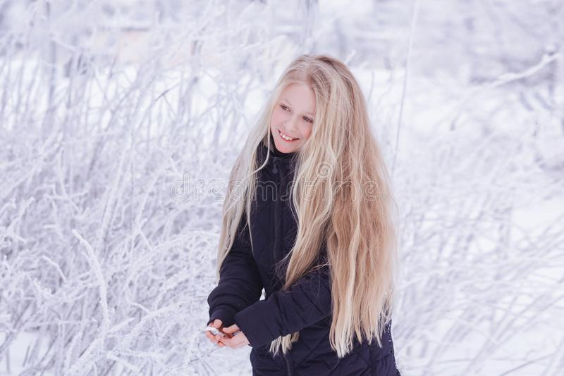 Winter girl blowing snow. Beauty Joyful Teenage Model Girl having fun in winter park. Beautiful girl laughing outdoors. Enjoying n royalty free stock photography