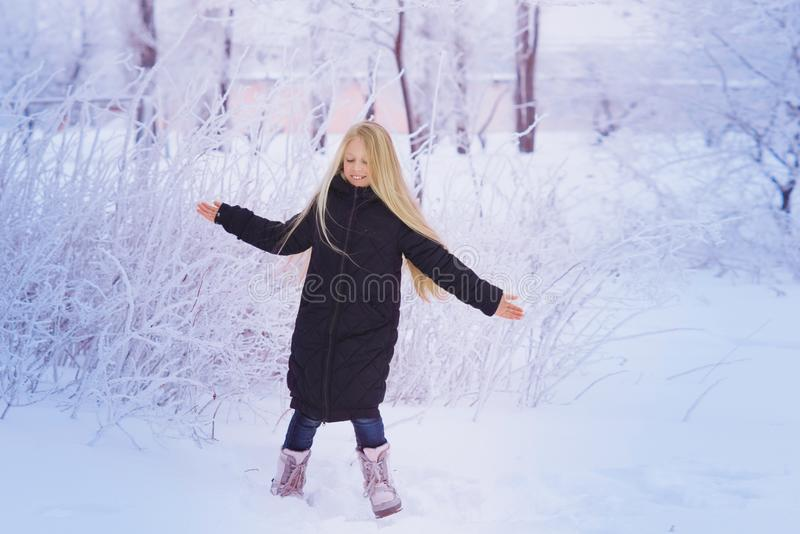 Winter girl blowing snow. Beauty Joyful Teenage Model Girl having fun in winter park. Beautiful girl laughing outdoors. Enjoying n royalty free stock images