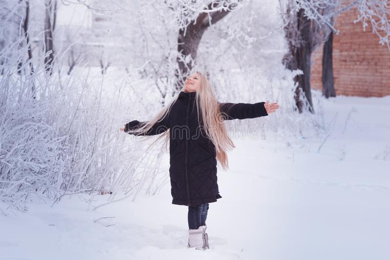 Winter girl blowing snow. Beauty Joyful Teenage Model Girl having fun in winter park. Beautiful girl laughing outdoors. Enjoying n royalty free stock photos