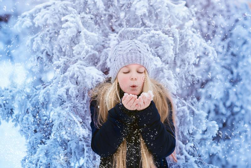 Winter girl blowing snow. Beauty Joyful Teenage Model Girl having fun in winter park. Beautiful girl laughing outdoors. Enjoying n stock image