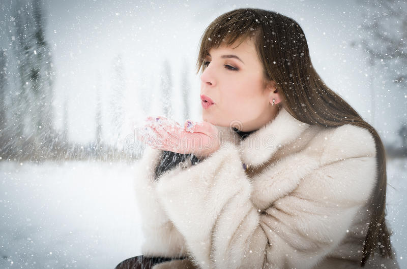 Winter girl blowing snow stock image
