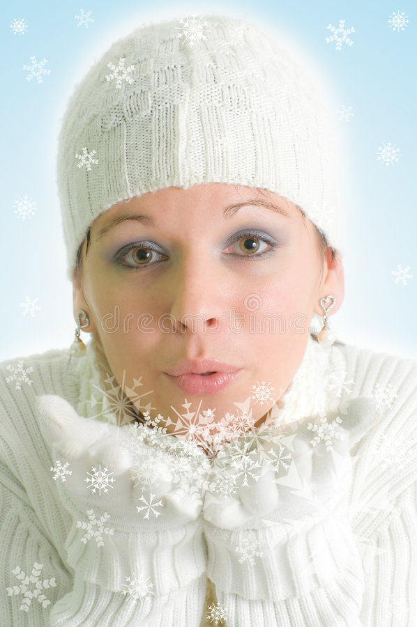 Winter girl blowing into snowflakes. Dreamy picture of attractive young girl blowing into snowflakes royalty free stock photo