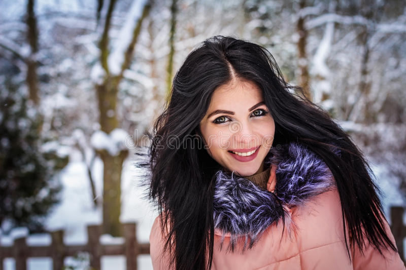Winter. Girl brunette capless smiles on the background of snow royalty free stock images