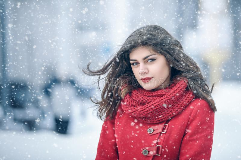 Winter. Girl brunette capless smiles on the background of snow. Close-up. hair develops stock photos