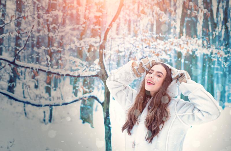 Winter girl. Model wearing stylish sweater and gloves. Joyful Beauty young woman Having Fun in Winter Park. royalty free stock photos