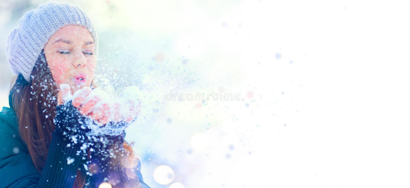 Winter girl portrait. Beauty joyful model girl blowing snow, having fun in winter park. Beautiful young woman enjoying nature royalty free stock photography