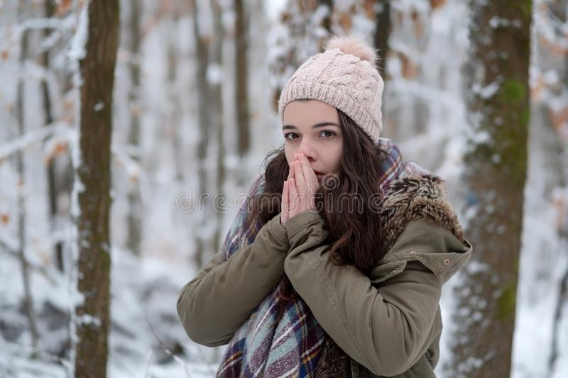 Winter girl portrait with scarf, hat in the cold in the winter forest rubs her hands royalty free stock photography