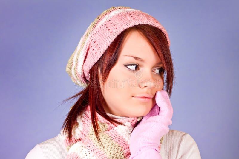 Winter girl on purple background. Cute winter girl looking to the left on purple background royalty free stock photo