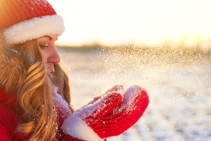 Winter girl in red blows in the palms of the snow in the warm sunset sun royalty free stock photos