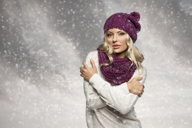Winter girl in white with purple hat and scarf. Young and blond girl wearing purple scarf and hat in winter dress over white stock photo